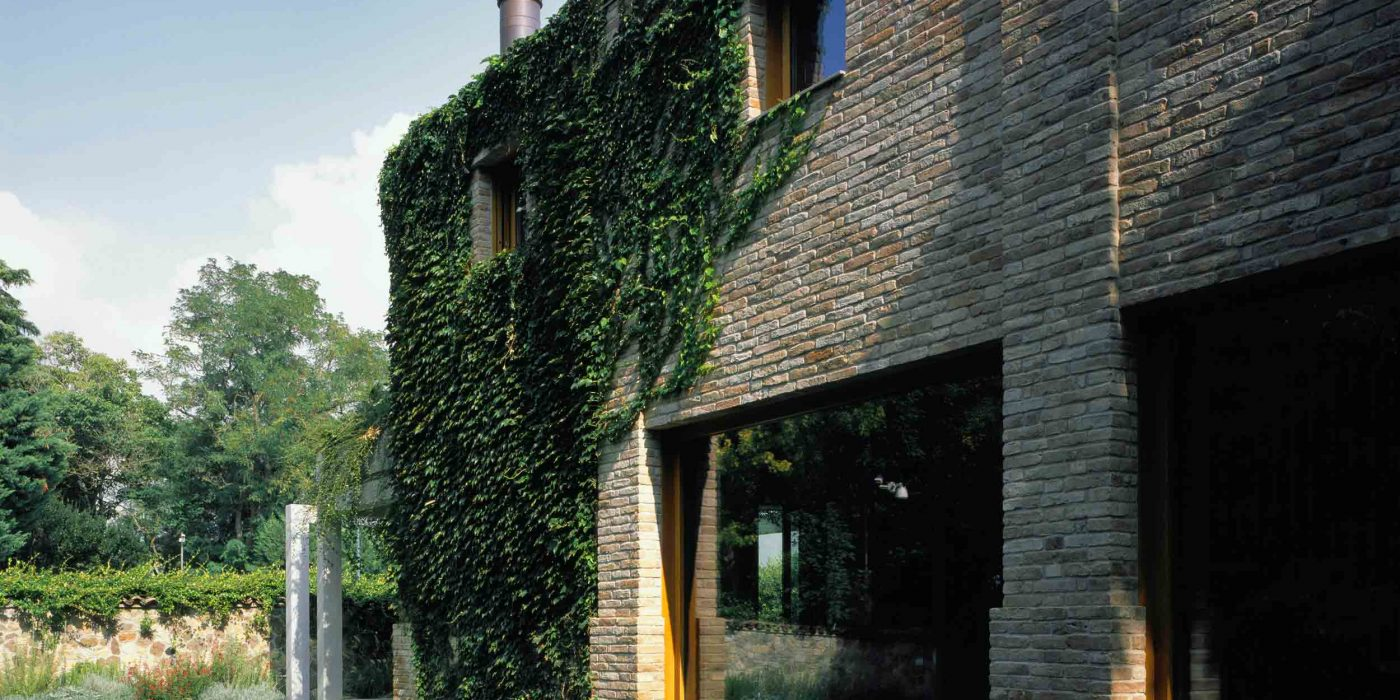 View of the side facade in recycled bricks with windows and fixed glass windows in oak wood
