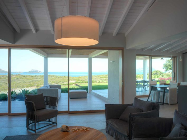 View of the living room of Villa Costa Smeralda with two sliding windows on the back wall