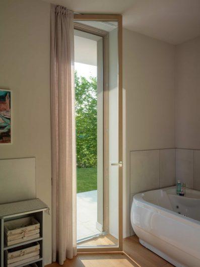 Vista della porta finestra del bagno in legno con finitura laccata a campione