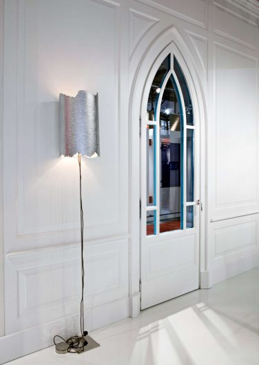 View of a wall with classic white boiserie and arched door