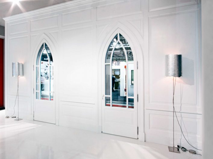 View of a wall covered with a white wood paneling with classic frames